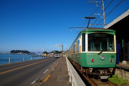 See the cute Enoden (street train) running on the road from Koshigoe to Enoshima!